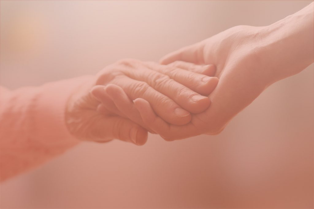 Caregiver and old patient holding hand