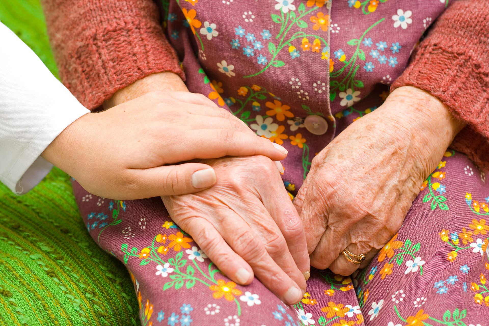 Caregiver and senior lady holding hands