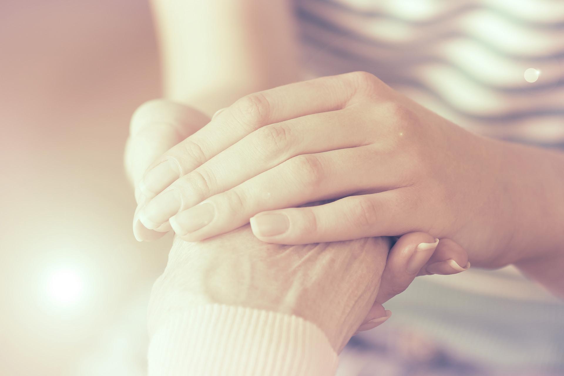 Caregiver holding senior patient hand