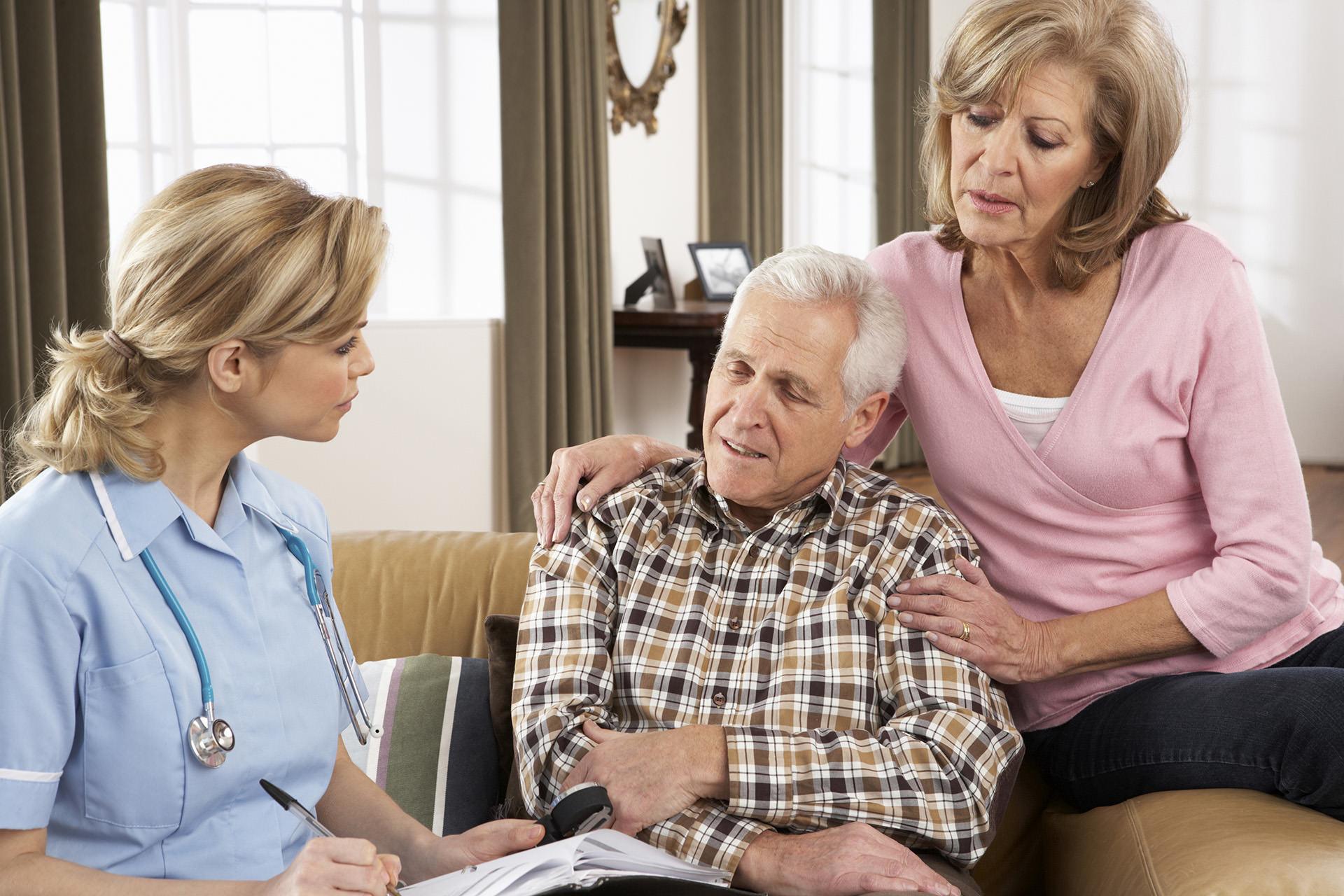 Caregiver nurse talking to senior man and women