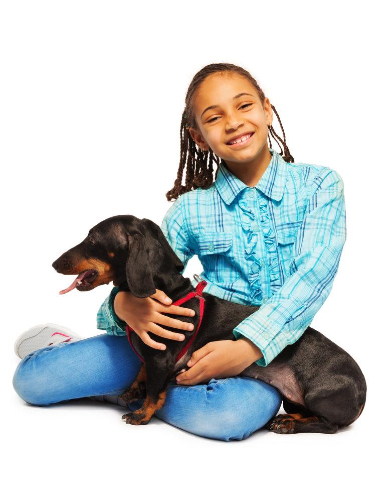 Girl hugging friendly black dog