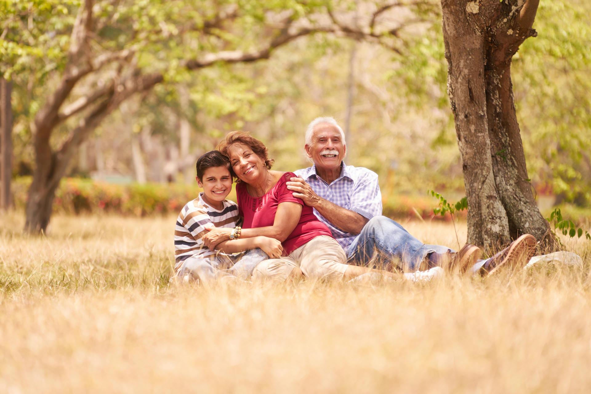 Senior Couple Hugging Boy On Grass