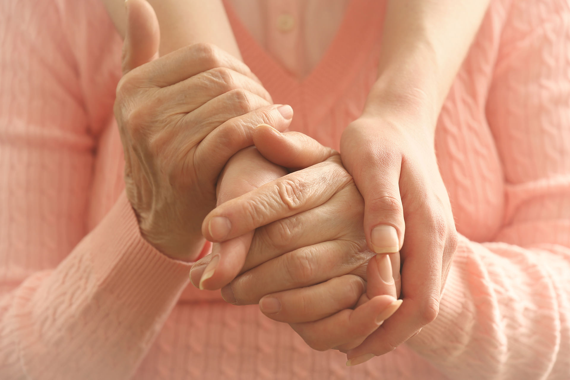 Senior patient and caregiver  holding hands